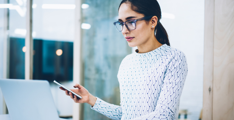 female bank employee logging into computer with mobile device in hand
