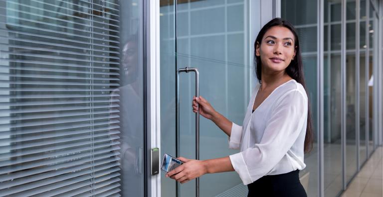 woman using mobile phone to unlock door
